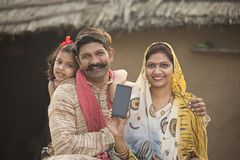 Famille rurale avec plaisir tenant le nouveau téléphone portable image libre de droits