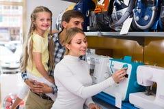 Famille sélectionnant la machine à coudre dans le magasin Images libres de droits