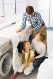 Famille sélectionnant le joint de blanchisserie Image libre de droits