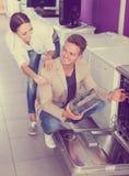 Famille sélectionnant le lave-vaisselle moderne Images stock