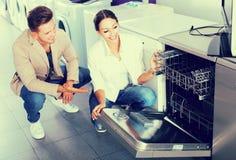 Famille sélectionnant le lave-vaisselle moderne Photo stock