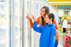 Famille sélectionnant les produits refroidis dans l'hypermarché Image stock