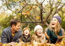 Famille s'étendant en parc avec le contour à la maison photographie stock libre de droits