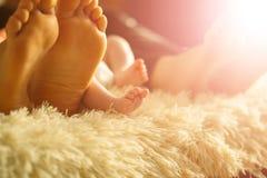 Famille s'étendant sur le lit, leurs pieds sur le foyer Mère, père et fils nouveau-né de bébé Photos stock