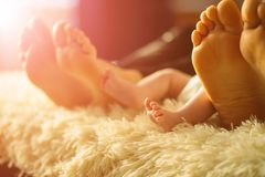 Famille s'étendant sur le lit, leurs pieds sur le foyer Mère, père et fils nouveau-né de bébé Photos libres de droits