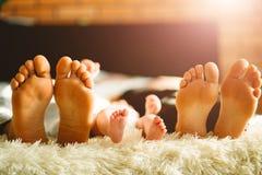 Famille s'étendant sur le lit, leurs pieds sur le foyer Mère, père et fils nouveau-né de bébé photo stock