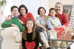 Famille s'asseyant autour d'une table basse Photos stock