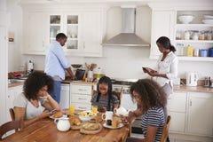 Famille s'asseyant autour du Tableau de petit déjeuner utilisant des dispositifs de Digital photo libre de droits