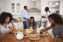 Famille s'asseyant autour du Tableau de petit déjeuner utilisant des dispositifs de Digital image stock