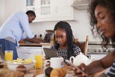 Famille s'asseyant autour du Tableau de petit déjeuner utilisant des dispositifs de Digital images libres de droits