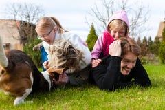 Famille s'asseyant avec des chiens ensemble sur un pré Photo stock