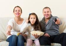 Famille s'asseyant avec le maïs éclaté Image libre de droits