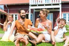Famille s'asseyant dans l'herbe à la maison mangeant la pastèque Image stock