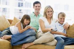 Famille s'asseyant dans la salle de séjour avec à télécommande Photographie stock