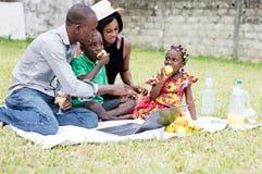 Famille s'asseyant dans le déjeuner de jardin ensemble image libre de droits