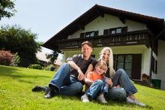 Famille s'asseyant devant leur maison Photographie stock libre de droits