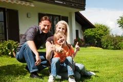 Famille s'asseyant devant leur maison Photo stock