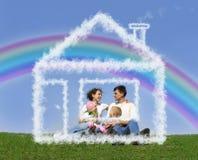 Famille s'asseyant en collage de maison rêveuse et d'arc-en-ciel Photographie stock libre de droits