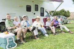 Famille s'asseyant en dehors de la maison de rv photographie stock