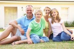 Famille s'asseyant en dehors de la maison rêveuse Photo libre de droits