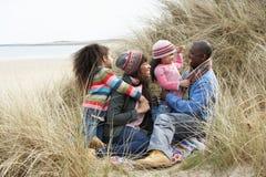 Famille s'asseyant en dunes appréciant le pique-nique l'hiver Image libre de droits