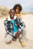 Famille s'asseyant en dunes sur la plage de l'hiver image stock