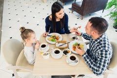 Famille s'asseyant ensemble à la table dans un restaurant Image stock