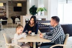 Famille s'asseyant ensemble à la table dans un restaurant Images stock