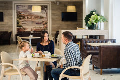 Famille s'asseyant ensemble à la table dans un restaurant Photographie stock
