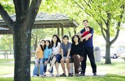 Famille s'asseyant ensemble sur le banc de pique-nique à l'extérieur Image libre de droits