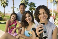 Famille s'asseyant à l'extérieur prenant le vidéo Image stock