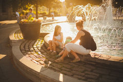 Famille s'asseyant par une fontaine Photographie stock