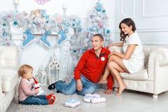 Famille s'asseyant près de l'arbre de Noël Photo libre de droits