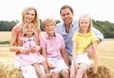Famille s'asseyant sur des balles de paille dans le domaine moissonné Photo stock