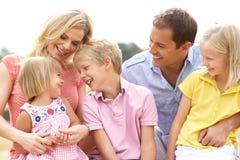 Famille s'asseyant sur des balles de paille dans le domaine moissonné Photo libre de droits