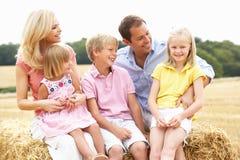 Famille s'asseyant sur des balles de paille dans le domaine moissonné Photos libres de droits