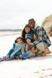 Famille s'asseyant sur la plage de l'hiver Photographie stock libre de droits