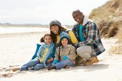 Famille s'asseyant sur la plage de l'hiver images stock
