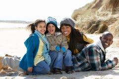 Famille s'asseyant sur la plage de l'hiver Photos libres de droits