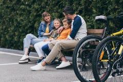 Famille s'asseyant sur le banc au parc, foyer sélectif sur des bicyclettes sur le premier plan photographie stock libre de droits