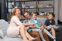 Famille s'asseyant sur le divan regardant TV, parents de sourire heureux passant le temps avec des enfants Image stock