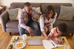 Famille s'asseyant sur le livre d'images de Sofa As Daughter Colors In photographie stock libre de droits