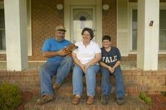 Famille s'asseyant sur le porche avant de la maison Image stock