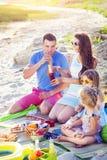 Famille s'asseyant sur le sable à la plage au pique-nique d'été Photographie stock