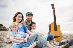 famille s'asseyant sur le sable avec une guitare sur le fond de plage Photographie stock