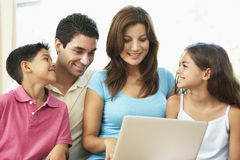 Famille s'asseyant sur le sofa à la maison avec l'ordinateur portatif Photo libre de droits