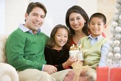 Famille s'asseyant sur le sofa retenant un cadeau de Noël Photo stock