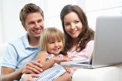 Famille s'asseyant sur le sofa utilisant l'ordinateur portatif à la maison Photos stock