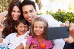 Famille s'asseyant sur Seat dans le jardin à la maison prenant Selfie Photo stock