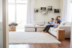 Famille s'asseyant sur Sofa At Home Watching TV ensemble photo libre de droits